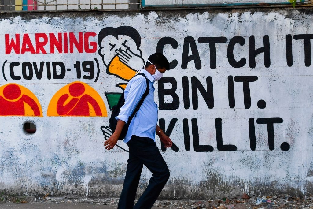 A pedestrian wearing a facemask amidst fears over the spread of the Covid-19 coronavirus walks past a wall graffiti creating awareness about the pandemic, in Mumbai on March 23, 2020.